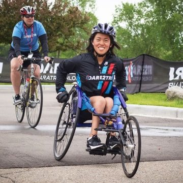 Smiling athlete crosses the finish line in a wheelchair