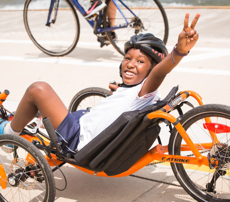 A youth athlete rides a recumbent and holds up a peace sign.