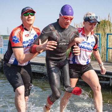 Volunteers helping athlete out of water